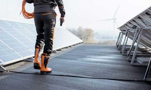 Worker Walking by Solar Panels