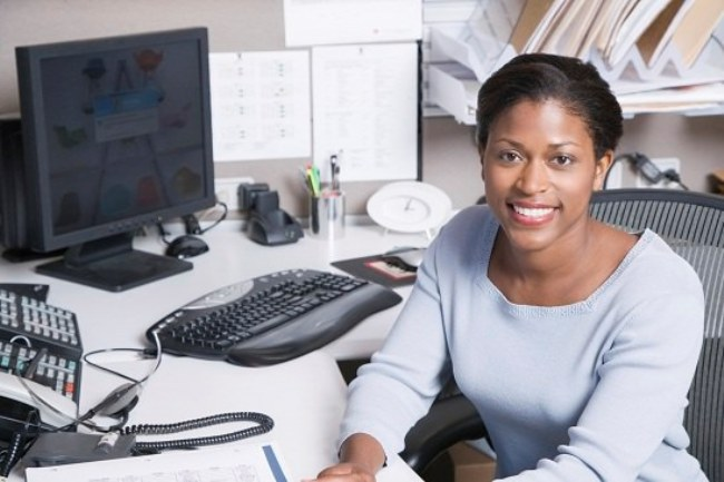Woman sitting at desk in office, smiling, portrait