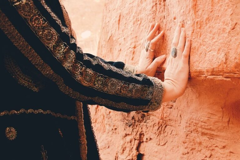 Hands resting against red rock wall.