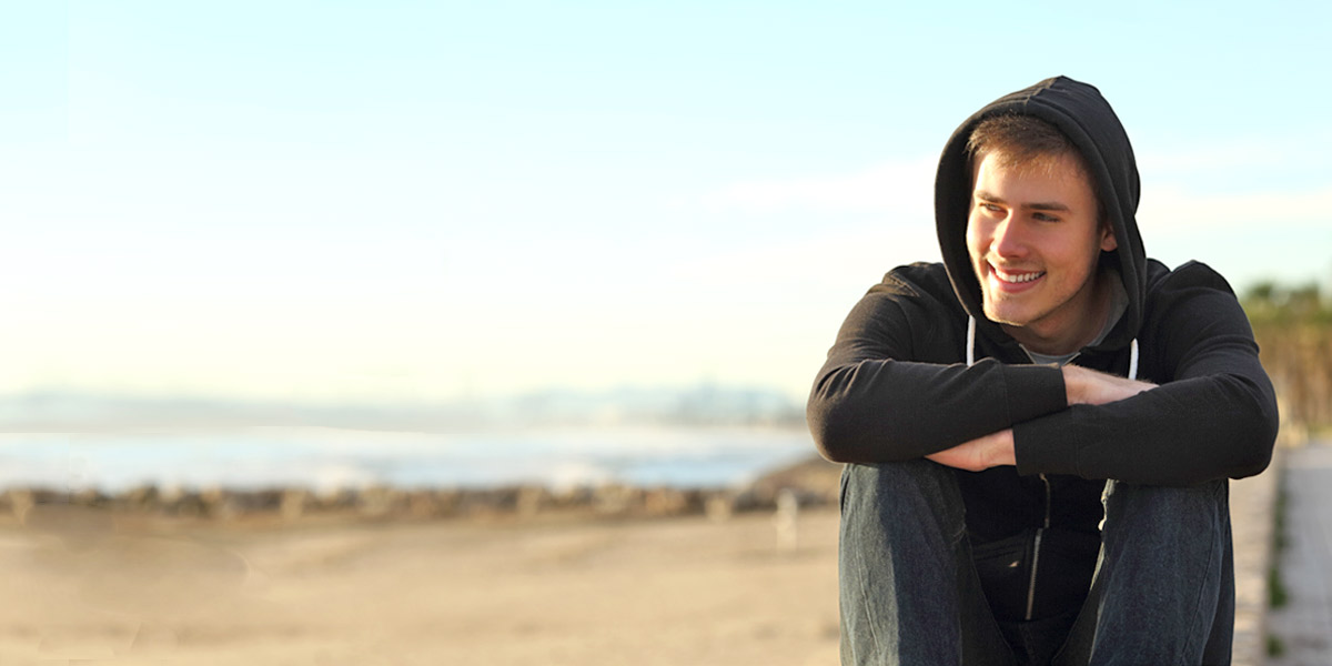 young man wearing hoodie sitting on beach smiling