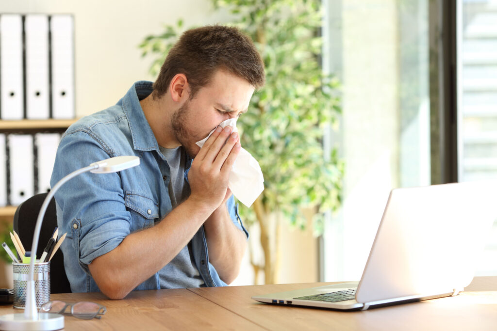 Ill entrepreneur sneezing at office