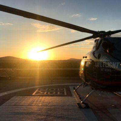 Emergency medical helicopter on helipad at sunset