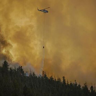 Helicopter dropping fire suppression over wildfire for the US Forest Service