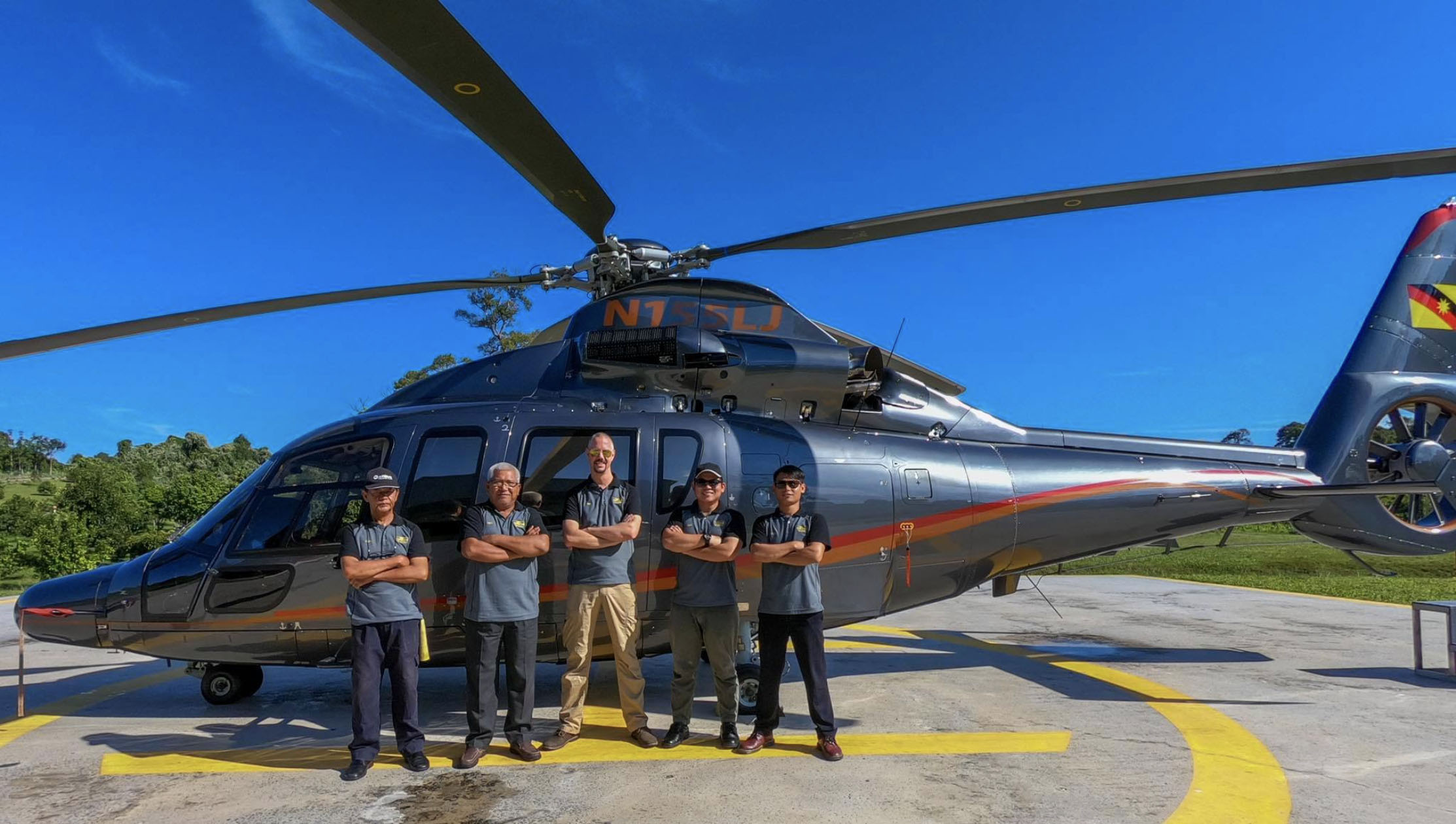 Group of Precision Aviation students standing in front of helicopter