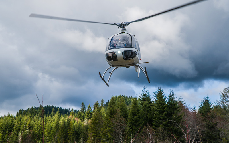 Foreign student pilot landing helicopter in forest terrain with Precision Aviation
