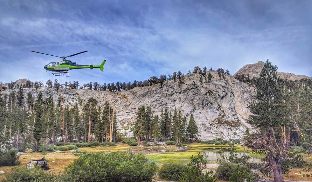 Green helicopter transporting equipment for USFS over mountain terrain
