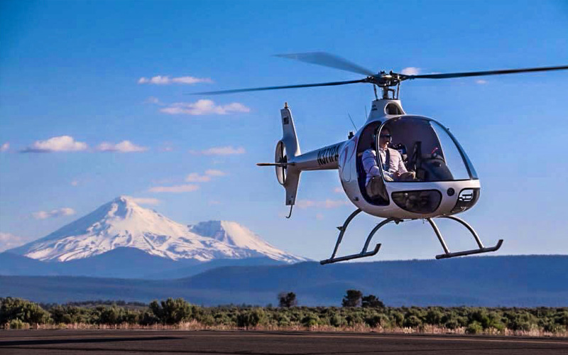 Student pilot landing a helicopter at Precision Aviation with view of Mt. Hood in the background