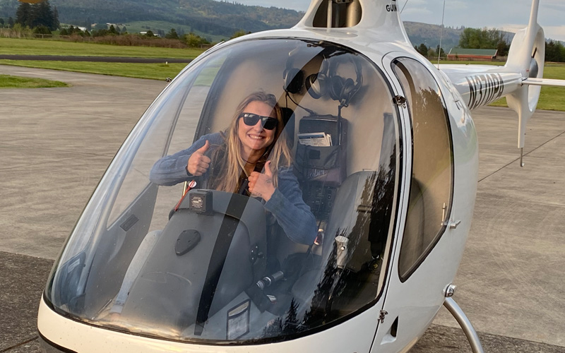 Student pilot giving thumbs up from the helicopter cockpit at Precision Aviation