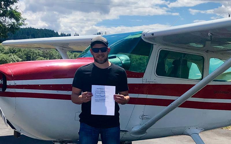 Veteran graduate holding aviation degree program certificate next to plane
