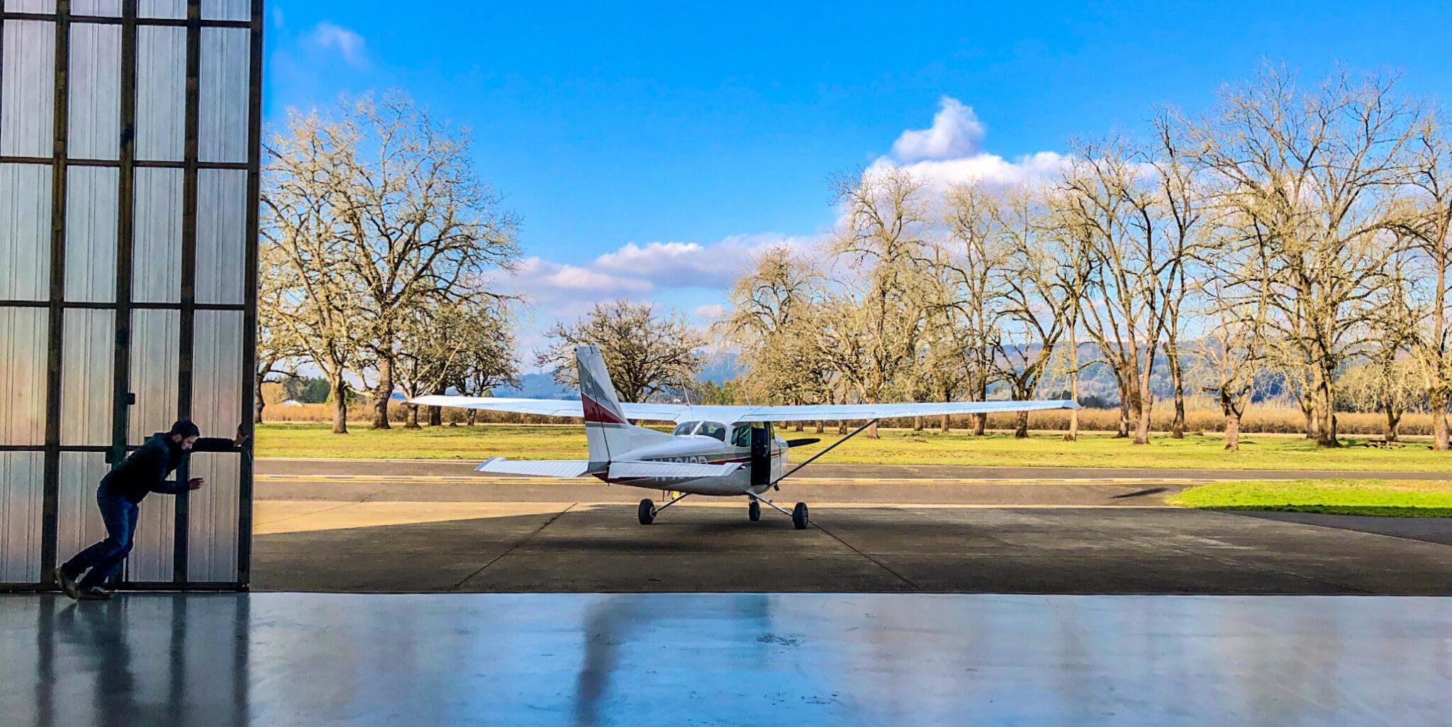 Plane leaving hangar for student pilot training at Precision Aviation