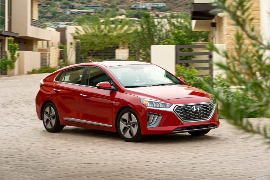 2020 Hyundai Ioniq Hybrid driving in red. (Side-view 3/4 view)   BEST Road-Trip Cars of 2020