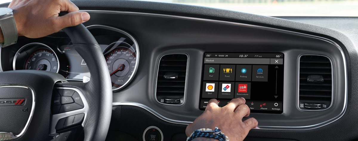2020 Dodge Charger/Challenger UCONNECT infotainment system with man tapping screen.   BEST Road-Trip Cars of 2020