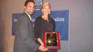 Alumnus Keith Alexander presents an SPJ award to Carol Dudley, career development director.