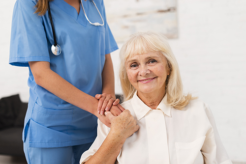Elderly woman sitting in chair with nurse nearby