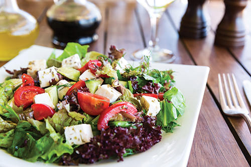 green salad mixture featuring feta cheese and tomatoes
