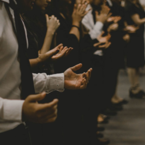 people in a row with hands up in prayer