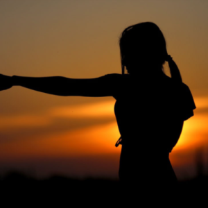 silhoutte of woman punching in karate stance