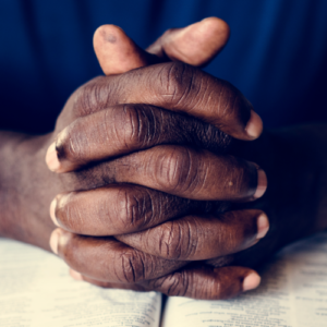 african american man holding hands over Bible in prayer