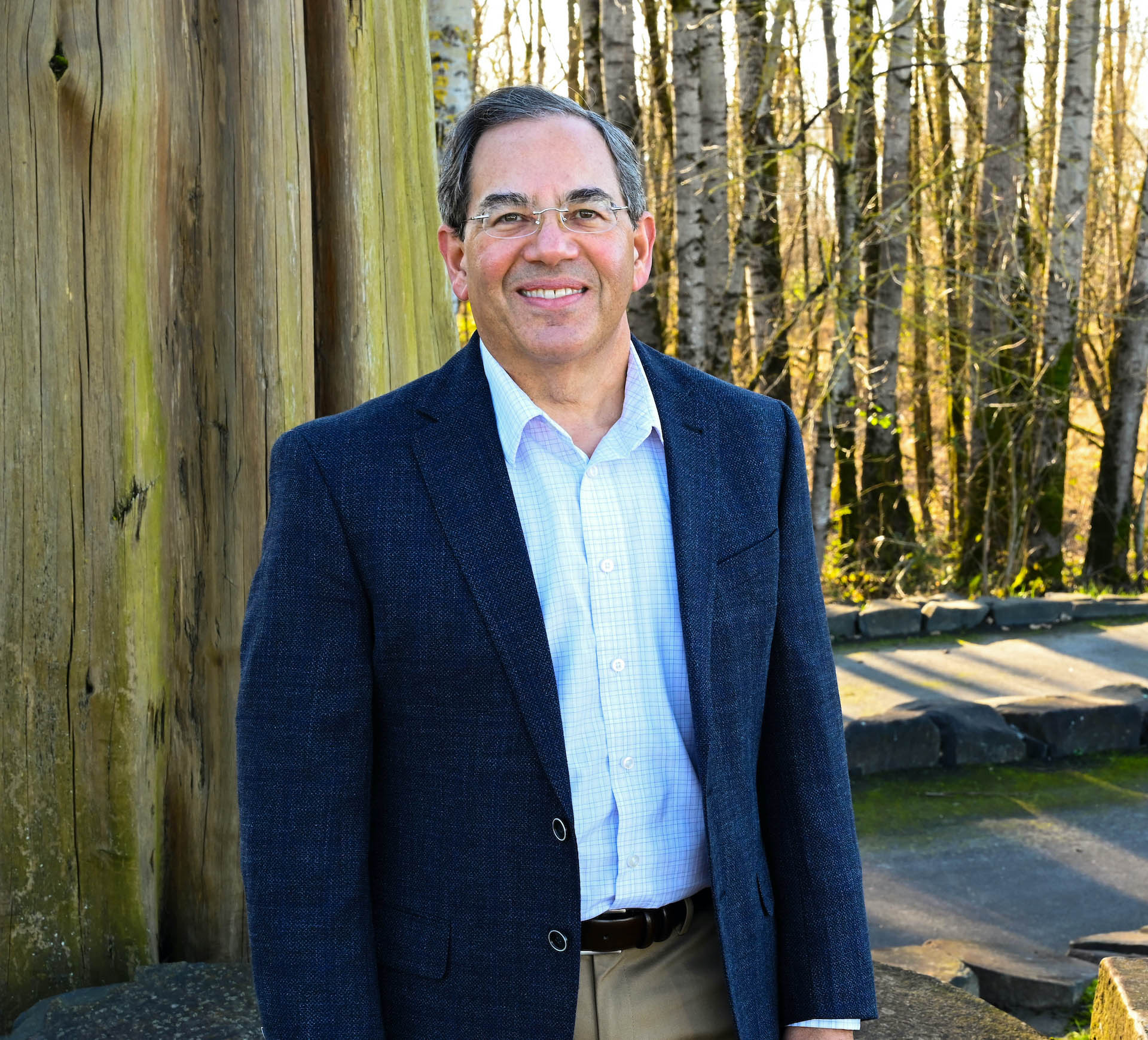 Ben Bierman consultant and founder of Integration Advantage is seen standing outside wearing a Blue Jacket and surrounded by trees and nature in the Pacific Northwest.