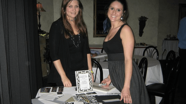 2 women standing by Memory Book table ready to help guests