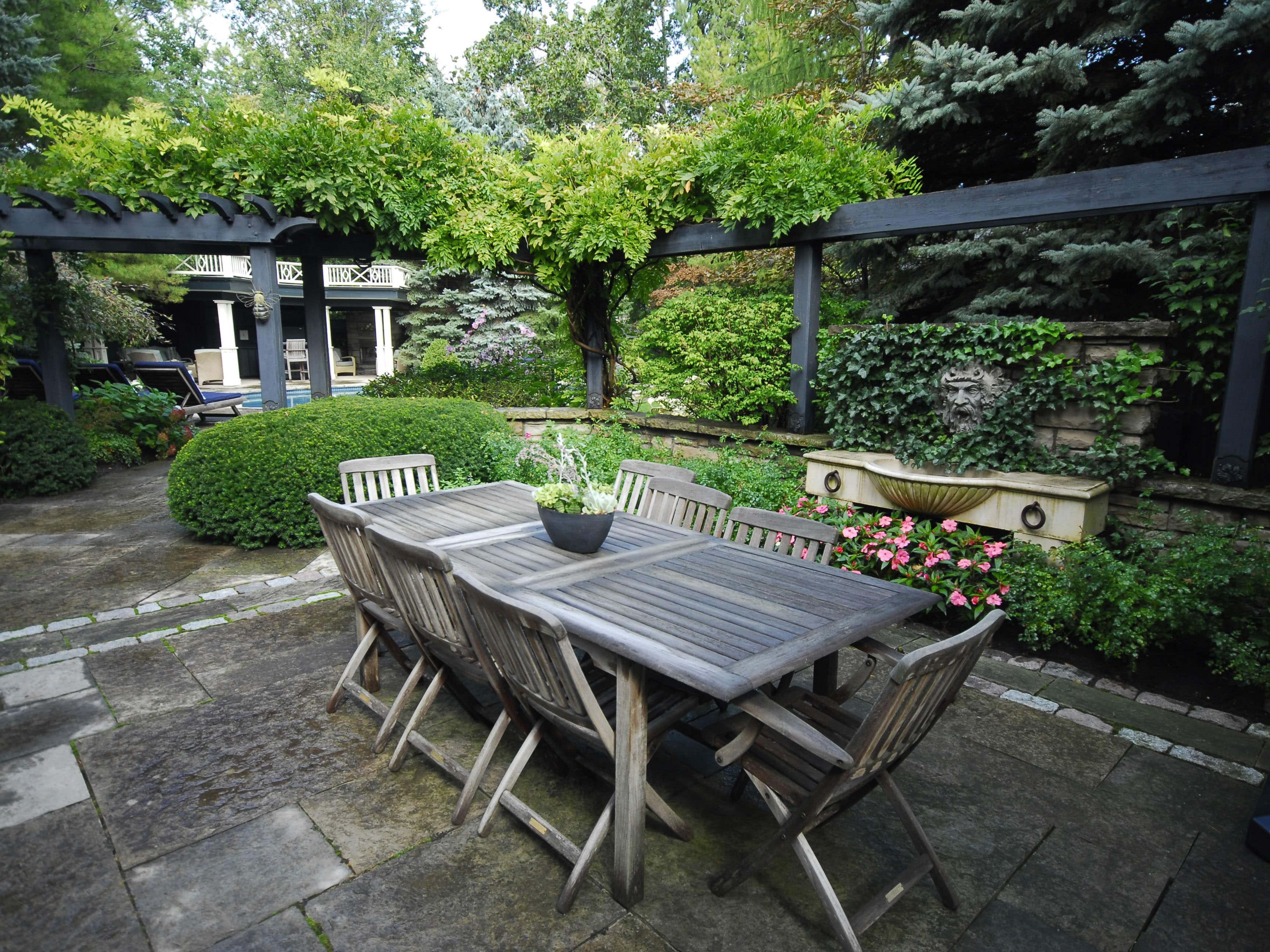 service: maintenance. Backyard wooden table and wooden chairs surrounded by greenery