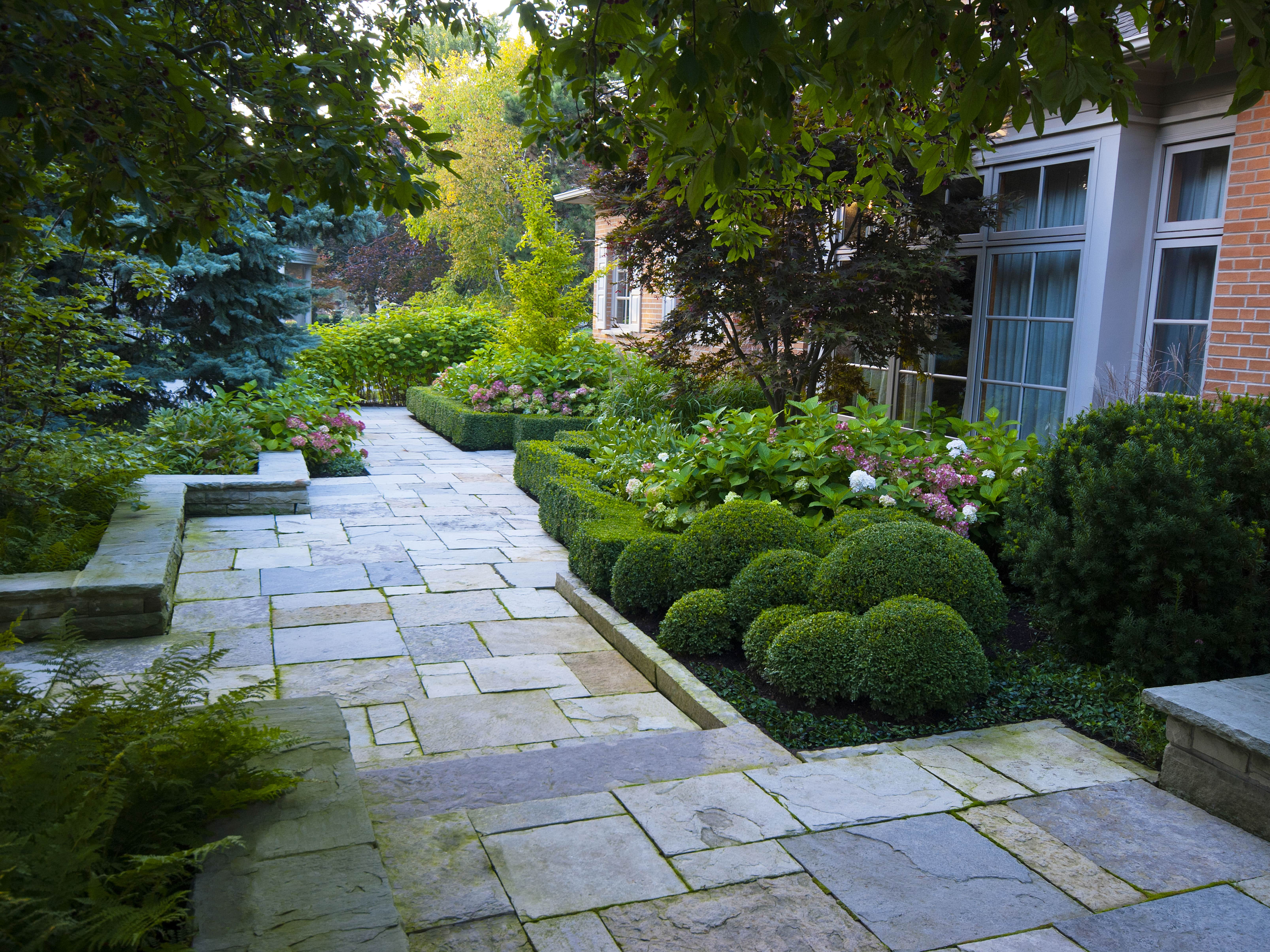 Service: Pruning. Well maintained garden with carefully pruned bushes and flowers.