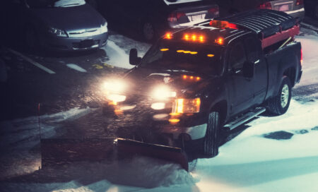 A snowplow operator clears a large snowfall from a parking lot at night.  Light grain.
