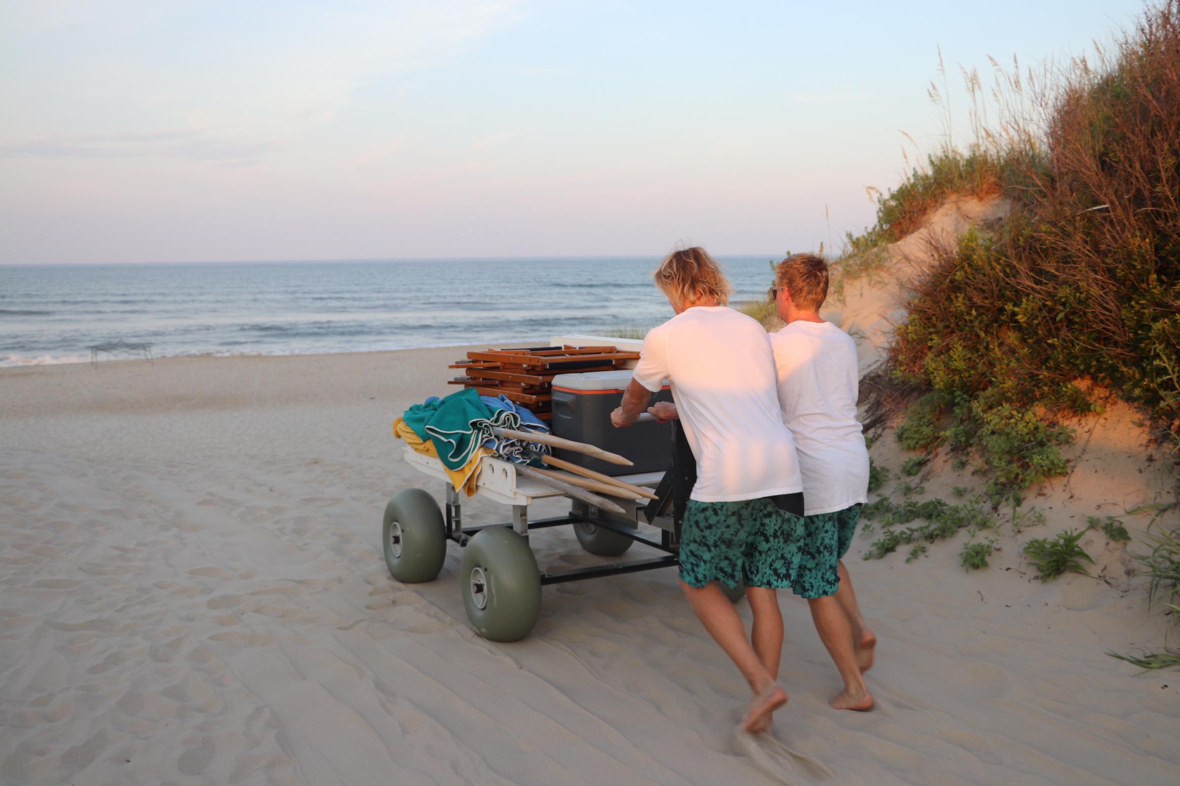 EnjoyTheBeach OBX staff members haul gear and beach equipment for OBX guests