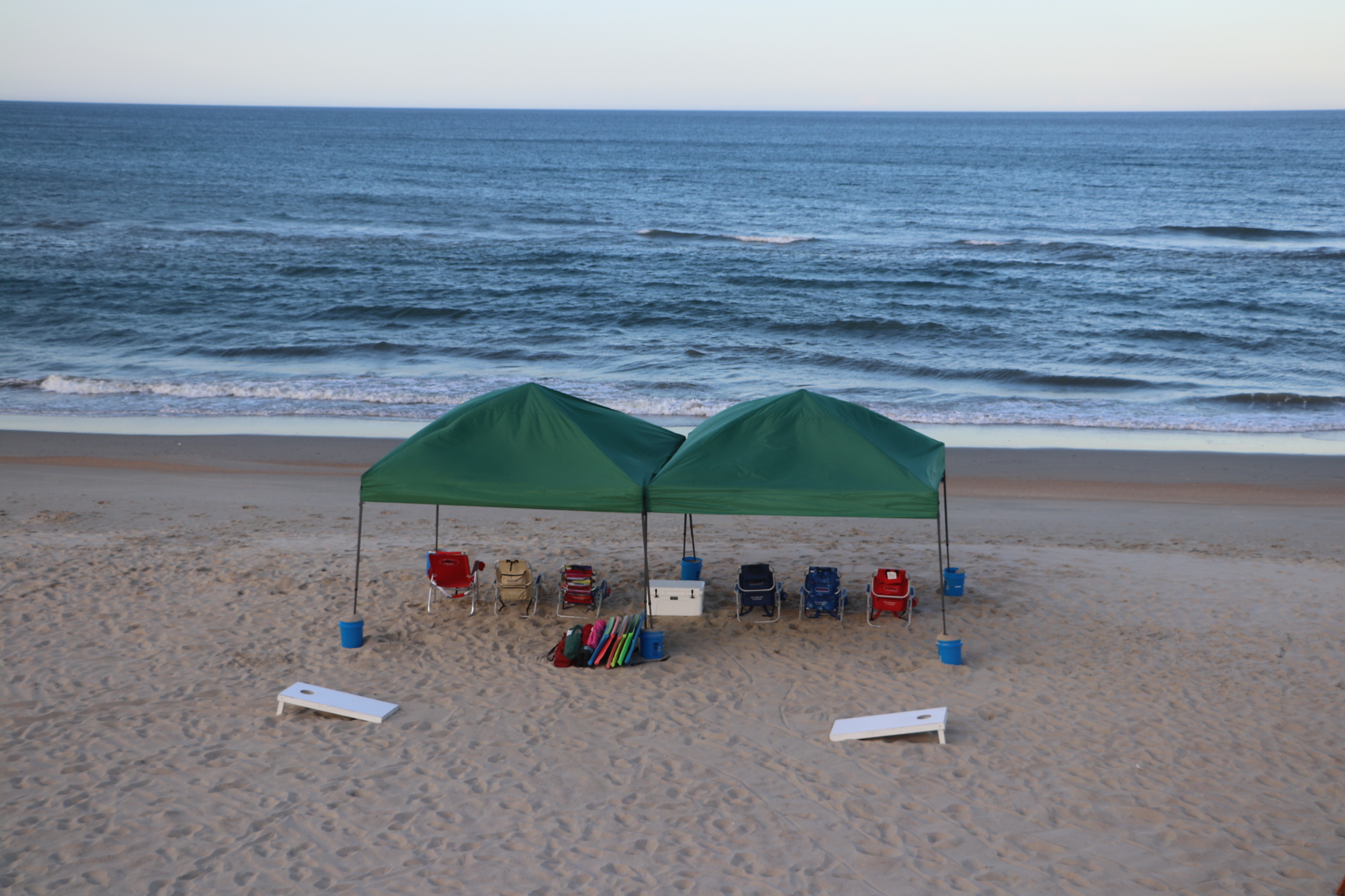OBX beach equipment set up with tents, chairs and cornhole game