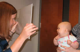 optometrist testing an infants visual acuity with a Teller card