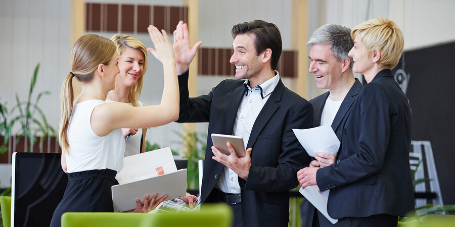 Successful team of business people giving high five in the office