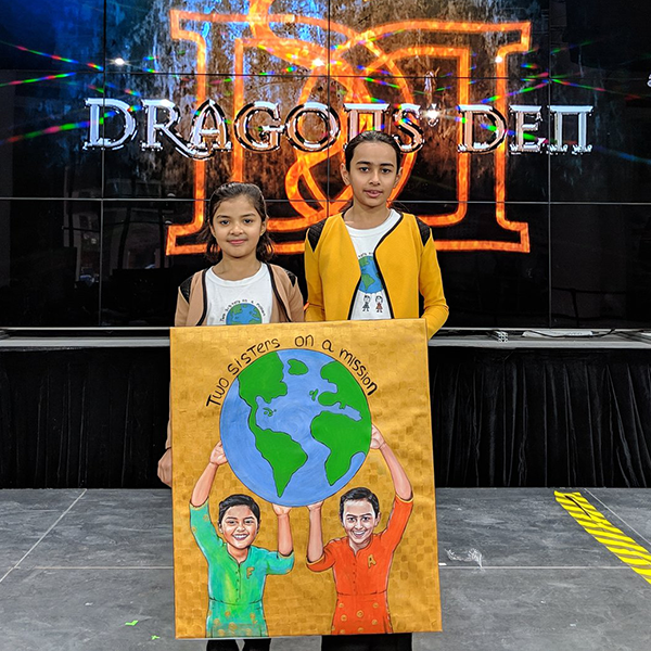 Fatima and Amna Sultan holding their book cover and standing in front of the Dragon's Den logo.