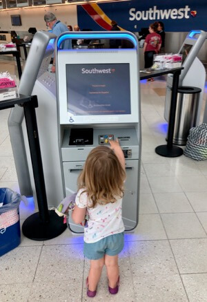 Young Southwest Companion Pass Holder Taking Ticket at the Kiosk