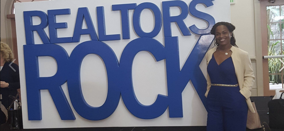 woman next to sign that reads Realtor's Rock