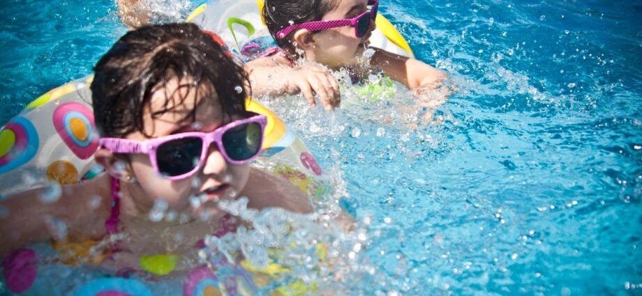 Two young girls in swimming pool with sunglasses and floats