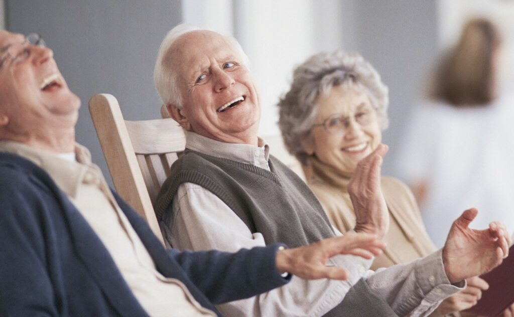 happy, laughing seniors sitting in chairs