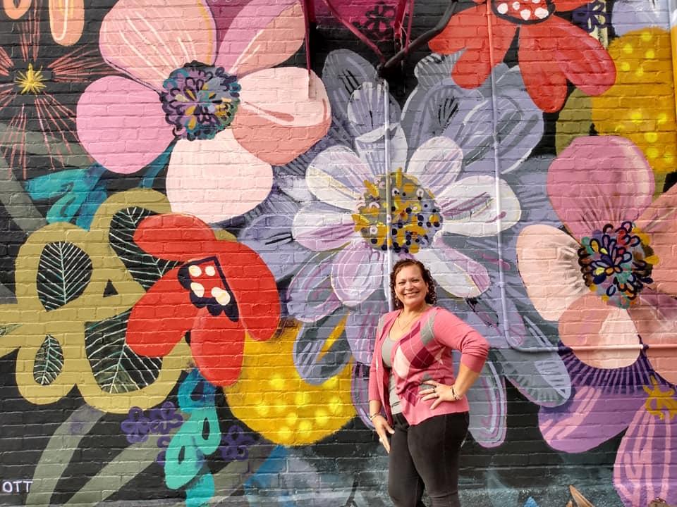 Evangeline standing in front of a mural of flowers by Cassandra Ott