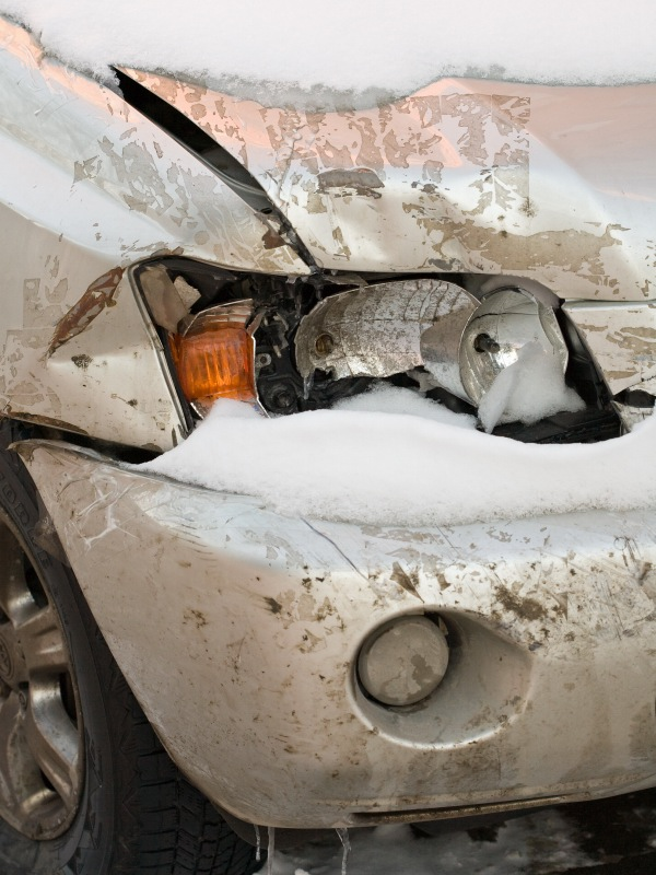 Broken Headlight on Snow-Covered Car