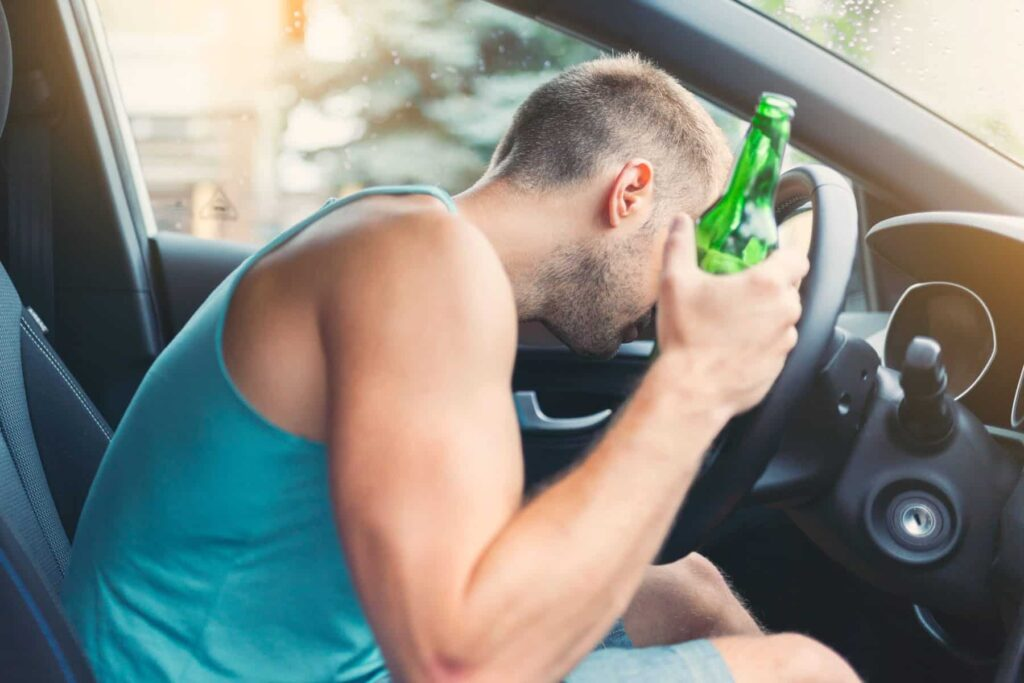 Driver holding a beer.