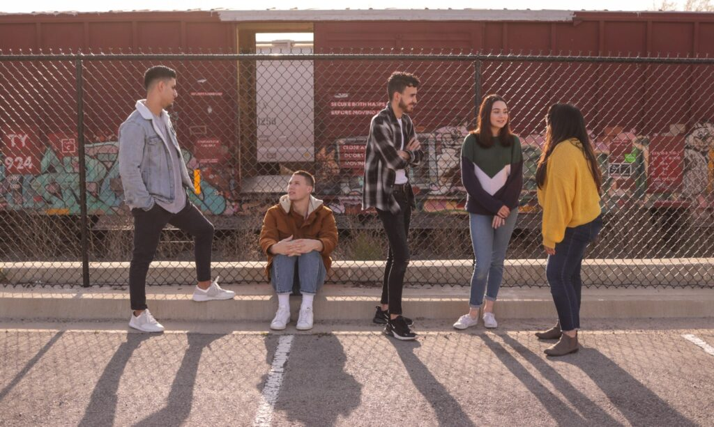 Photo of teens standing together by a fence.