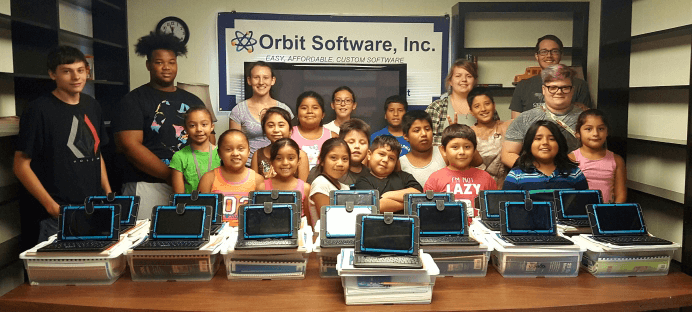 ACLAMO students, Orbit teachers and ACLAMO assistants pose behind the tablets and study books awarded during the program.