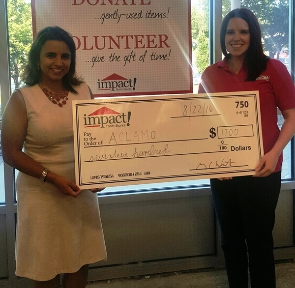 Nelly Jimenez has reason to smile as she accepts a $1,700 check from Thrift Impact's Lindsay Varzaly.