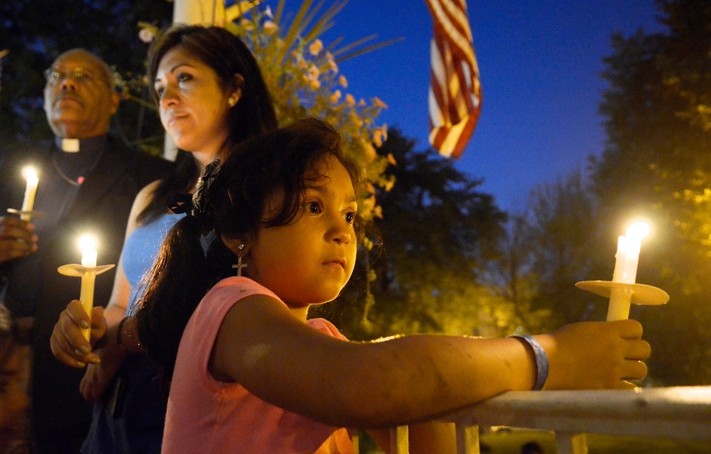 An eight-year-old girl holds a candle representing her deported father during an immigration reform rally