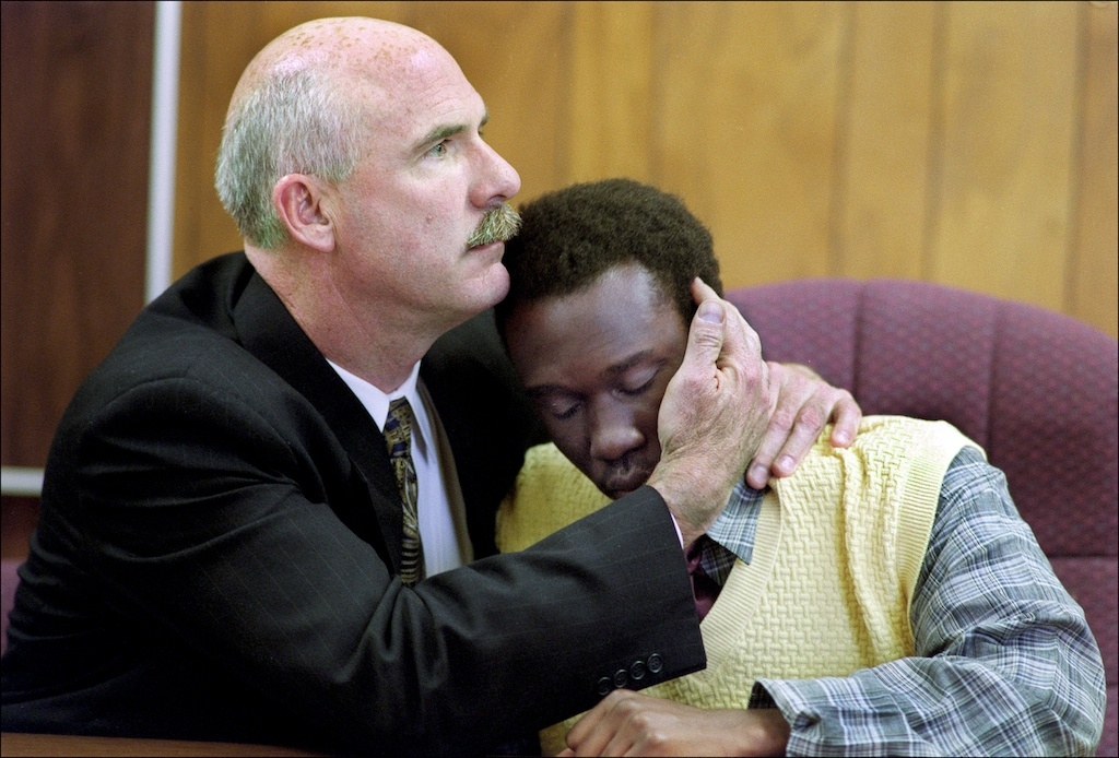 A defense lawyer hugs a young defendant as he enters a guilty plea for killing a girl