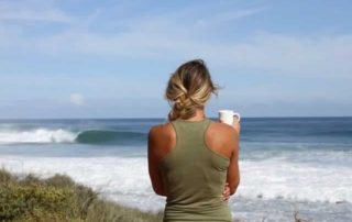 Woman overlooking ocean with a cup of coffee