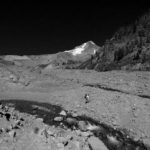 Hiker crosses a wide gully with braided streams on the south side of Mount Hood. Mount hood, a pyramid standing above the hiker.