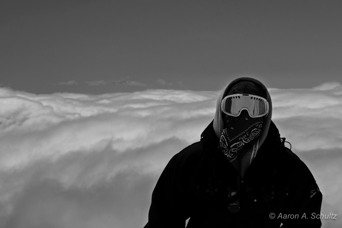 A snowboarder on a mountain seems to floats above the clouds. Mount Hood, Oregon.