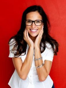 Portrait of smiling young woman wearing glasses against red background