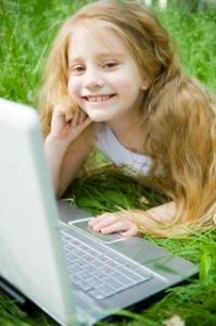 Smiling little girl with laptop in green grass