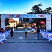 Runner crosses 3M Half Marathon finish line